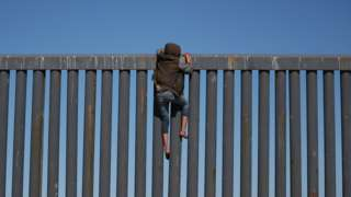 A migrant, part of a caravan of thousands from Central America trying to reach the United States, climbs the border fence