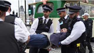 Police remove a demonstrator from a bus parked on London Bridge