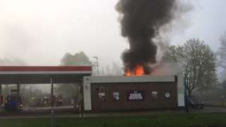 Flames and smoke emerging from the roof of the Esso petrol station shop building.