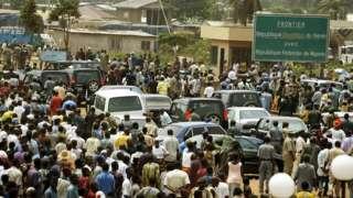 President Olusegun Obasanjo as im dey cross di Benin-Nigeria border to go settle kwanta over criminals wey dey use di border anyhow