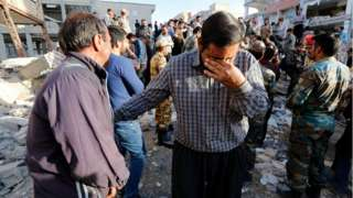 Iranian victims of the earthquake mourn near the wreckage of their home in the city of Pole-Zahab, in Kermanshah Province, Iran, 13 November 2017