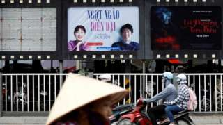 """Bikers go past an empty space where a promotional poster for """"Abominable"""" stood before being taken down at a cinema in Hanoi"""