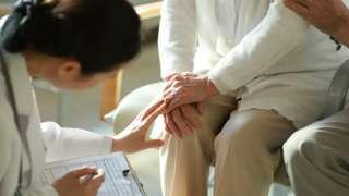 Médica de costas e sentada examina joelho de idosa sentada