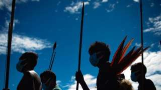 Indígenas Yanomami enfileirados na contraluz, com céu azul atrás