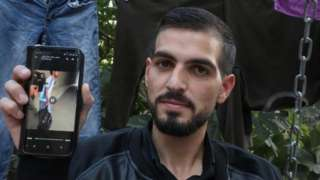 Qawasmi displays on his phone a video leaked online apparently showing a border guard shooting him in the back