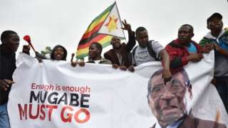 """People wave a Zimbabwean national flag and carry banners during a demonstration demanding the resignation of Zimbabwe""""s president on November 18, 2017 in Harare."""