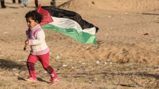A Palestinian girls runs with the national flag, as protesters burn tires at the site of a tent protest on April 8, 2018, on the Israel-Gaza border east of Rafah in the southern Gaza Strip