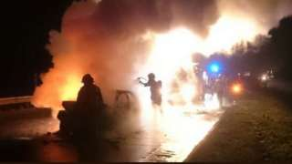 Firefighters tackle a car on fire