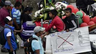 """Colombian indigenous people hold a sign reading: """"Let not the weapons silence us"""" during the funeral of Kevin Mestizo and Eugenio Tenorio,"""