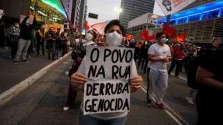 Manifestante segura cartaz onde se lê 'o povo na rua derruba genocida'