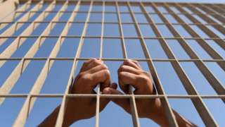 A person's hands are seen holding the bars in this photo