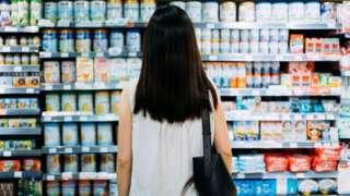 Mulher diante de prateleira de supermercado