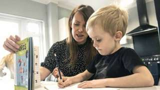Little boy working on schoolbook with mother at home