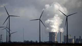 Wind turbines are seen near the coal-fired power station Neurath, Germany