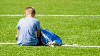 Boy siting on field