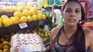 Victoria no supermercado, segurando uma bandeja de ovos