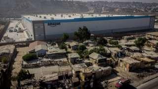 멕시코 티후아나에 있는 아마존 거대 물류 센터는 인근 빈민촌과 극명한 대조를 이룬다