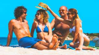 Four people in a beach in Greece