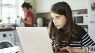 child on laptop being home schooled