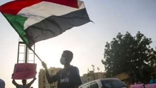 Man waves a Sudanese flag in Khartoum (file photo)