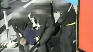 Leon Briggs being carried by police officers to police van