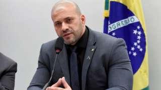 Daniel Silveira em sala da Câmara, falando em microfone e sentado, com bandeira do Brasil atrás