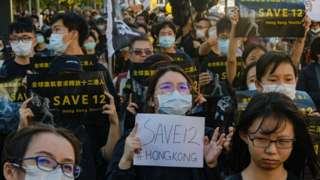 Taiwanese and local Hong Kong residents march in Taipei holding placards in support of the 12 Hong Kong democracy activists