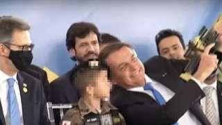 Reprodução de vídeo no Youtube mostra Bolsonaro sorrindo e apontando arma para cima, ao lado de criança e homens