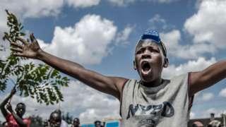 A Kenyan gestures as he protests about the police beating someone during curfew - May 2020