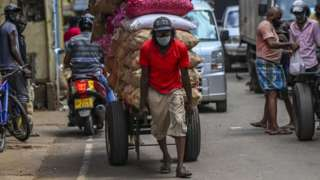 A labourer pulls a cart loaded with vegetables at the main market in Colombo on August 31, 2021 following Sri Lanka's declaration of state of emergency over food shortages as private banks ran out of foreign exchange to finance imports.