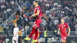 Serbia player Stefan Mitrovic grabs the banner at the stadium in Belgrade, 14 October