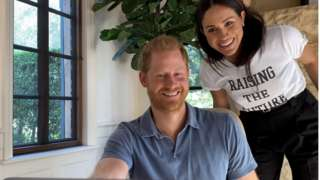Harry and Meghan, who is wearing a T-shirt emblazoned with the 'raising the future' logo