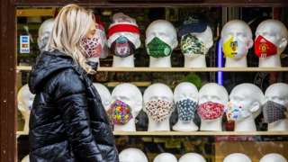 A woman walks past face coverings on display at a Belfast newsagent