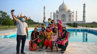 A group of tourists take photos as they pose in front of the Taj Mahal in Agra, India