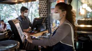 A woman working at the cashier at a restaurant wearing a facemask