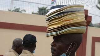 And on Wednesday a hawker in the Nigerian city of Lagos tries to sell hats to protesters opposing calls to reduce the country's minimum wage set at ($65; £45) a month.