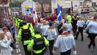 The police walk alongside members of Clyde Valley Flute Band during the Apprentice Boys parade