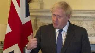 Boris Johnson gesticula enquanto fala em sala requintada