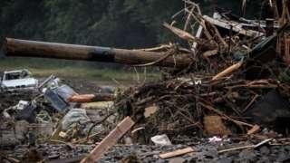 Destroços e pedaços de madeira amontoados perto de carro quebrado