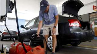 A man fills gallons of gasoline in the city of Ponce, on the south coast of Puerto Rico