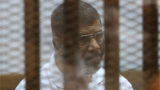 Mohammed Morsi in defendant's cage during a court appearance