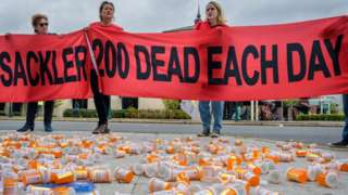 """Protesters at Purdue Pharma HQ holding a sign reading: """"Sackler 200 dead each day"""""""