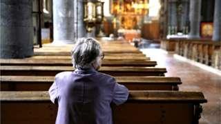 홀로 교회 예배당에 앉아있는 여성