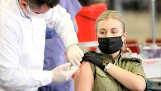 Members of uniformed services receive the AstraZeneca Covid-19 vaccine at the National Stadium in Warsaw