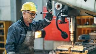 Older man working on a drill bit.