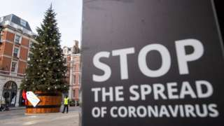 A Christmas tree is seen alongside coronavirus signage in Covent Garden, London