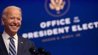 Joe Biden sorri diante de logo do escritório de presidente eleito