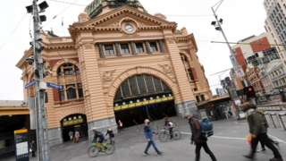 People pass Flinders Street Station in Melbourne during lockdown