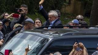 Lula deixando velório do neto, Arthur, escoltado pela polícia, sob o olhar de militantes e apoiadores