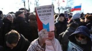 Женщина держит экземпляр Конституции России
